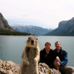 Landscape photo of couple in front of mountains and lake with squirrel taking centre stage.